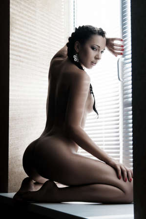 beautiful nude young woman on the window sill venetian blind