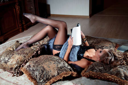 young woman lying and reading magazine indoor shot photo