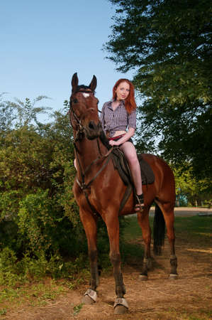 Beautiful woman with red hair sitting on a horse photo