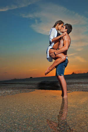 embraces: young couple kissing at the beach with the sun setting behind them