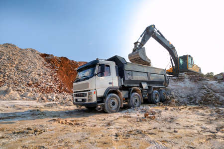 loading a large lorry building material, clay pit