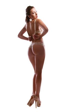 deseo sexual: Hermosa morena quita un sost?n sobre fondo blanco