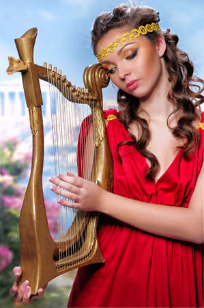 cute girl in a red tunic with a harp on a background of Greece photo