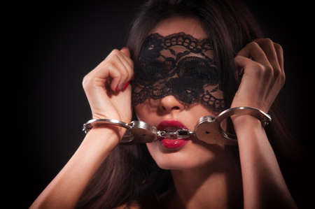girl in a black mask and handcuffed