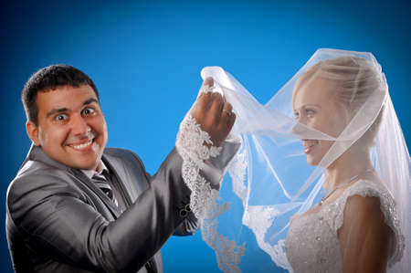 Loving newlyweds standing on a blue background