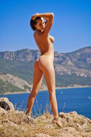 giovane nuda: Nuda donna giovane in piedi su una roccia