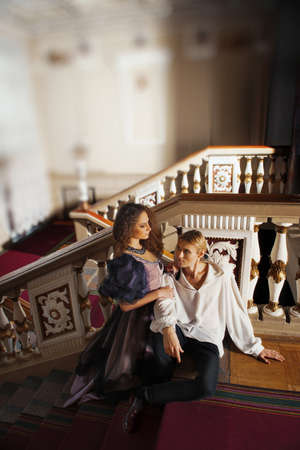 Beautiful couple in the clothing of the 18th century in a luxurious interior photo