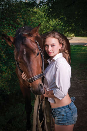 beautiful girl in a shirt and a horse near the tree photo