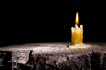 old candle stands on the stump of a tree on the black background photo