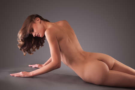 beautiful naked woman is lying, gray background
