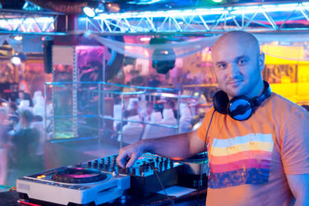 Male DJ stands for remote control indoor nightclub photo