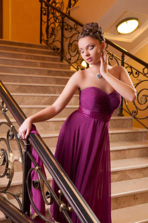 attractive young woman: attractive young woman in a beautiful dress sloit on the stairs in the hotel lobby