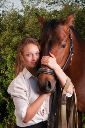 Beautiful young woman and horse. Nature, trees, sky. photo