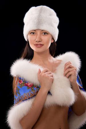 Winter girl with white fur hat wearing warm fur coat Stock Photo