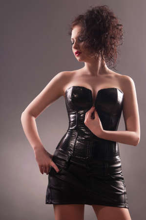 girl in a dress of black latex, gray background photo