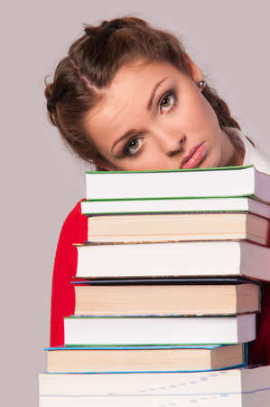 beautiful girl sitting in front of books, grey background photo