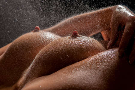 Wet breasts of a young sexy woman in front of black background