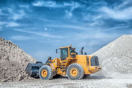 Wheel loader excavator with backhoe unloading clay Stock Photo