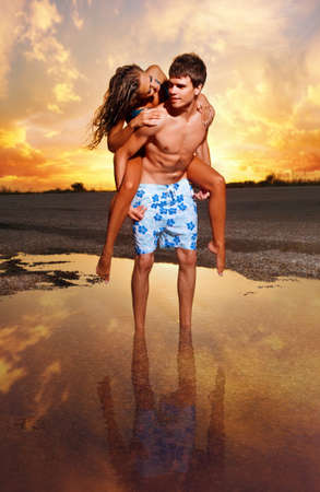 young couple kissing at the beach with the sun setting behind them photo