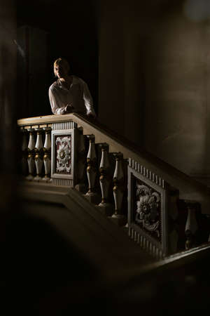 Beautiful man in the clothing of the 18th century in a interior with stairs photo