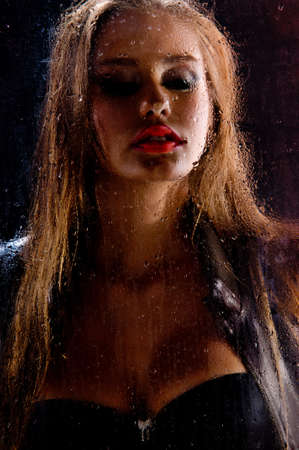 Beauty portrait of gorgeous woman behind rainy glass photo
