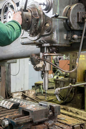 making hole: industrial technician working on a drilling machine - making a hole in a metal bar Stock Photo