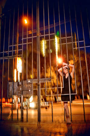 gripping bars: Emotions. Pretty woman posing in cage outdoors at night