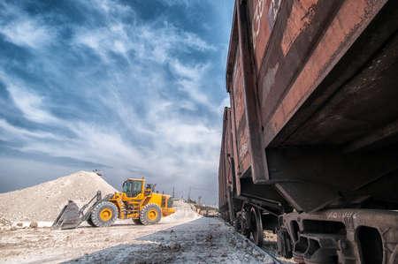 unloading: Wheel loader excavator with backhoe unloading clay Stock Photo