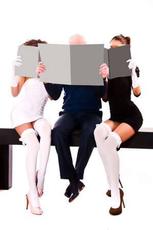 Two women and a man are holding gray magazines photo