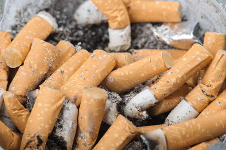 Detail of an ashtray with many burnt cigarettes. photo