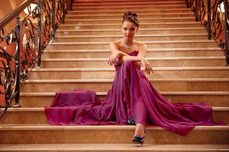mujer joven con un vestido largo tirado en las escaleras en el vestíbulo del hotel