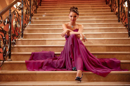 stairs interior: young woman in a long dress lying on the stairs in the hotel lobby