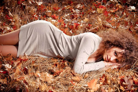 lying on leaves: woman in elegant clothes lying on the leaves