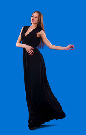 Elegant girl in fluttering black dress on a blue background photo