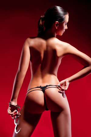 lesbian erotic: sexy buttocks and hands in manacle on a red background