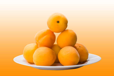organic background: ripe peach in white glass plate on yellow table