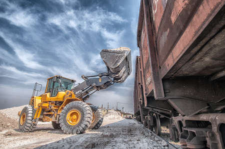 Wheel loader excavator with backhoe unloading clay 스톡 콘텐츠