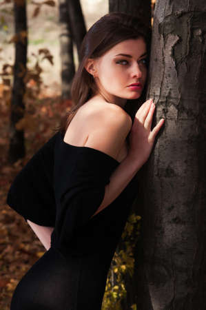 A young beautiful woman out alone in the autumn forest photo