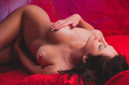 nude female buttocks: beautiful naked young woman on a red background Stock Photo