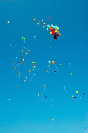 anniversaire: un grand nombre de ballons color�s dans le ciel bleu
