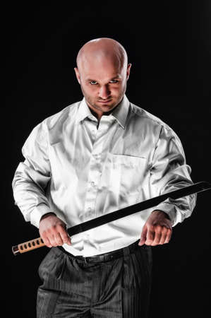 fighting styles: Male businessman wearing a suit to have the sword of Japanese samurai