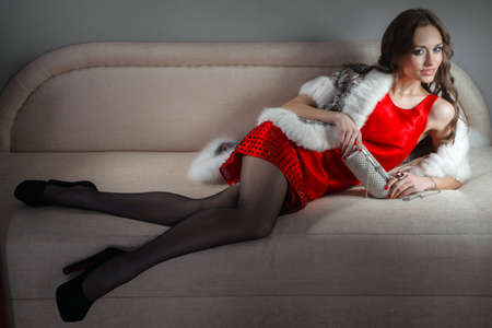 red sofa: alluring woman in red dress relaxing on a sofa