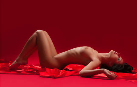 beautiful naked young woman on a red background photo