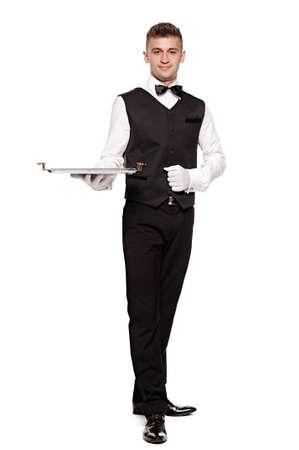 uniform: Un camarero o camarero o siervo sosteniendo una bandeja de plata y sonriente. Fondo blanco.