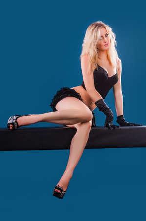 Una bella giovane donna fare sport su sfondo blu