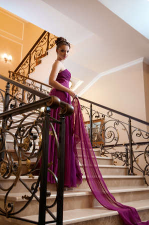 young woman in a long dress lying on the stairs in the hotel lobby photo