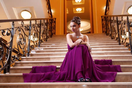 woman in a long dress is sitting on the stairs in the hotel lobby photo