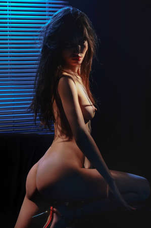 nude young girl stand before venetian blind in dark photo