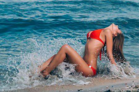 Mooie jonge vrouw, liggend op het strand Stockfoto