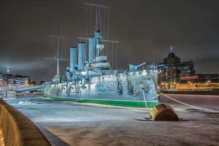 Cruiser Aurora at night in St. Petersburg. The inscription on the ladder: 1 rank cruiser of the Baltic Fleet Aurora